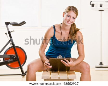 Woman holding stopwatch and clipboard - stock photo