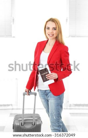 Woman holding suitcase on light background - stock photo