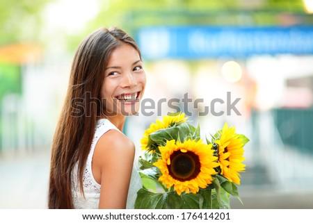 Woman holding sunflower flower smiling happy outdoor on beautiful summer day. Joyful multiracial Asian Caucasian female model in Kurfurstendamm, Berlin, Germany, Europe. - stock photo