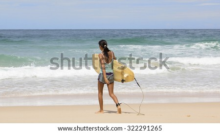 woman holding surf board go to the sea