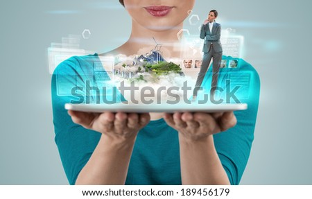 Woman holding tablet computer with holographic project of island and buildings making a business presentation - stock photo