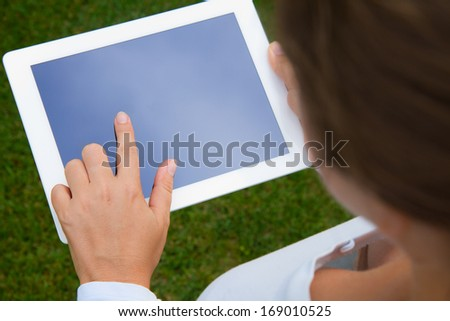 woman holding tablet PC on green grass lawn with copy space - stock photo
