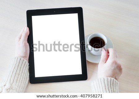Woman holding tablet pc, working at the desk with a cup of coffee.