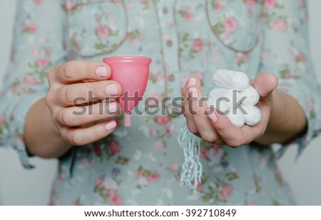 Woman holding tampons and menstrual cup in hands