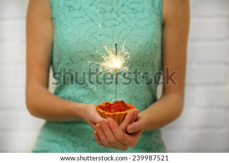 Woman holding tasty cake with sparkler, on grey wall background - stock photo