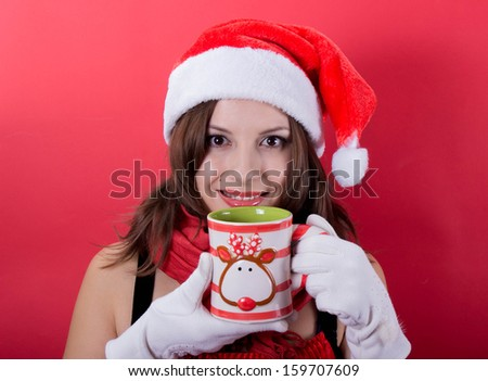 Woman holding tea cup on red background - stock photo