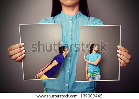 woman holding the lacerated photo of young couple in quarrel - stock photo