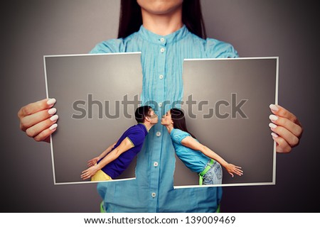 woman holding the lacerated photo of young kissing couple - stock photo