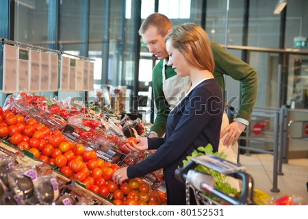Woman holding tomato while standing with shop worker in grocery store - stock photo