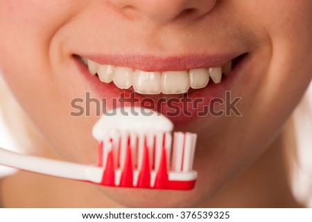 Woman holding toothbrush with toothpaste in front of teeth promoting mouth hygiene for healthy teeth. - stock photo