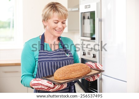 Woman Holding Tray With Home Made Loaf Of Bread - stock photo