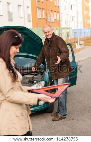 Woman holding triangle sign repairman fixing car breakdown problem crash - stock photo