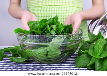 Woman holding tuft of sorrel in glass basin
