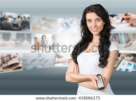 Woman holding TV remote control.