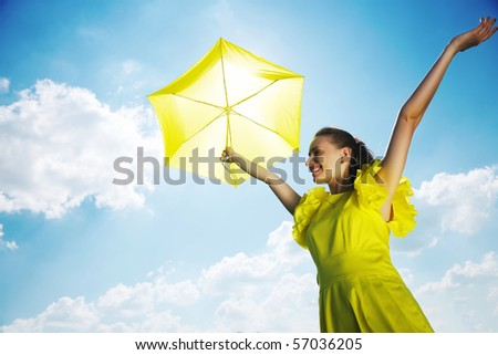 Woman holding umbrella against sun and sky - stock photo