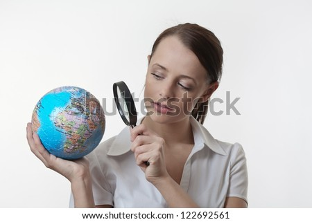 woman holding up a jigsaw globe puzzle and looking at it with a inspecting eye with a magnifying glass
