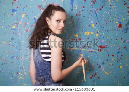 woman holding up a paintbrush - stock photo
