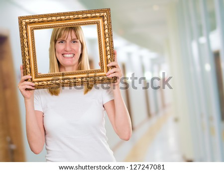 Woman Holding Up A Picture Frame in a hall - stock photo