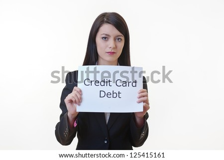 woman holding up a piece of paper with the words credit card debt written on it and tearing the sheet of paper in half - stock photo