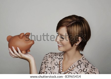 woman holding up a piggy bank - stock photo
