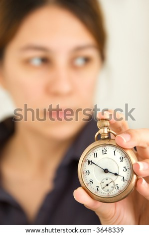 Woman holding up a pocket watch - focus on watch - stock photo