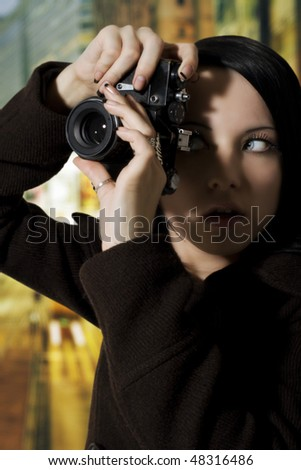 Woman holding up a retro camera about to take a photo. - stock photo