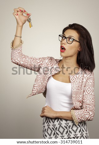 woman holding up a set of keys belonging to her house or car in her hand - stock photo