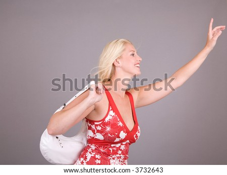 Woman holding up her hand to hail a bus or a taxi - stock photo