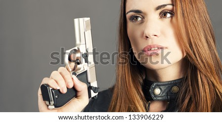 woman holding up her weapon - stock photo