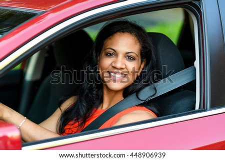 Woman holding up keys to her new car - stock photo