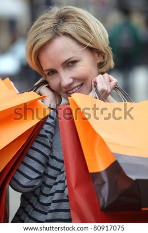 Woman holding up shopping bags - stock photo