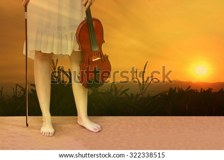 woman holding violin with meadow in sunrise background