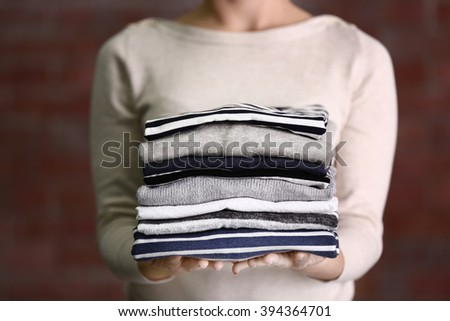Woman holding washed and dried clothes on brick wall background - stock photo