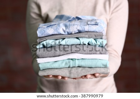 Woman holding washed and dried clothes on dark background - stock photo