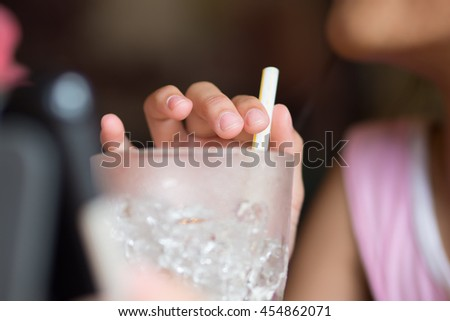 woman holding water in glass with straw