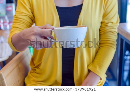 woman holding white cup of coffee in coffee cafe - stock photo