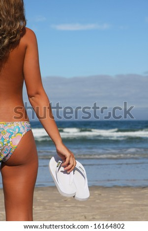 woman holding white flops on the shoreline - stock photo