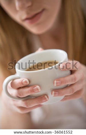Woman holding white mug with coffee - stock photo
