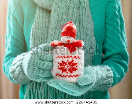 Woman holding winter cup with nice Christmas toy close up on light background. Woman hands in woolen teal gloves holding a cozy mug with happy snowman toy. Winter and Christmas time concept.  - stock photo