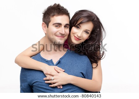 woman holding with love her boyfriend from behind, posing at camera - stock photo