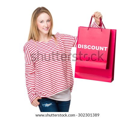 Woman holding with shopping bag and showing discount - stock photo