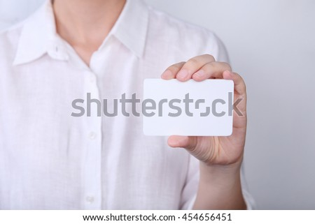 Woman holding with showing front view of white card