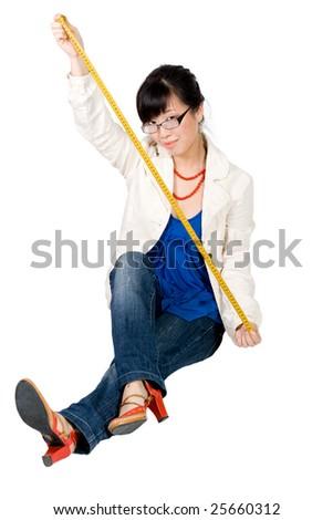 Woman holding yellow santimetre sitting on the floor - stock photo