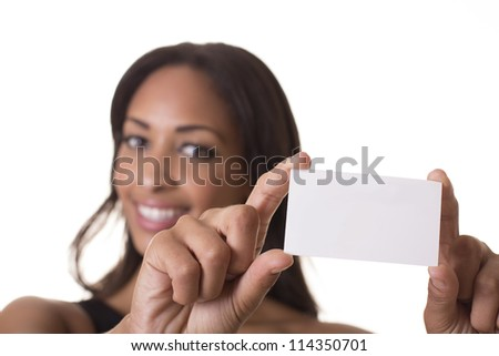 Woman holds a blank business card out in front of her smiling face. - stock photo