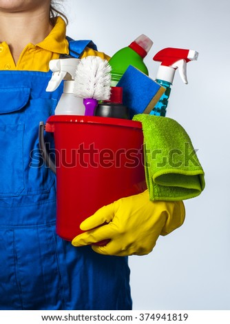 Woman holds a bucket of supplies for cleaning. Isolated on white background.