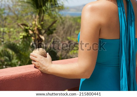 Woman holds a coconut water while looking out at the ocean and tropical landscape - stock photo