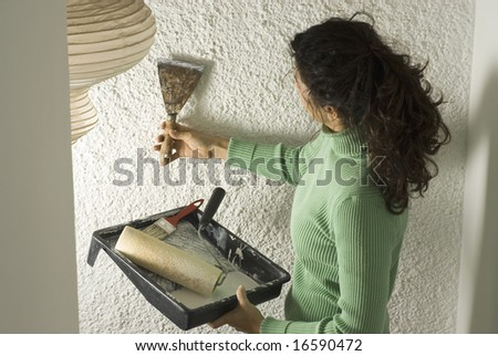Woman holds a scraper and scrapes wall while holding paint tray and roller. Vertically framed photo. - stock photo
