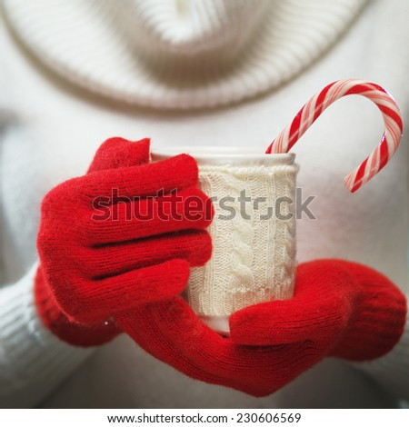 Woman holds a winter cup close up. Woman hands in woolen red gloves holding a cozy mug with hot cocoa, tea or coffee and a candy cane. Winter and Christmas time concept.   - stock photo