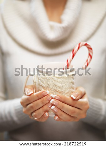 Woman holds a winter cup close up. Woman hands with elegant french manicure nails design holding a cozy knitted mugwith cocoa, tea or coffee and a candy cane. Winter and Christmas time concept.  - stock photo