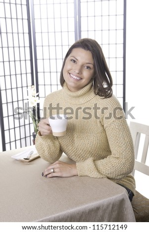 Woman holds coffee cup.
